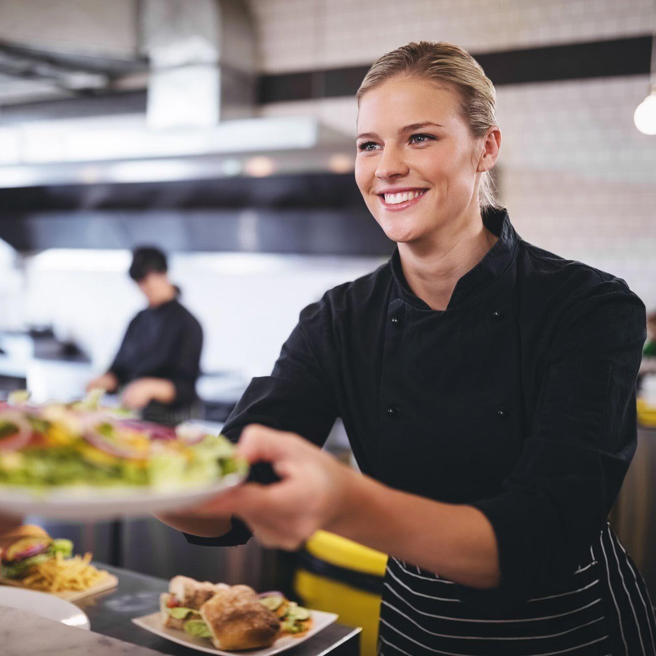 Lächelnde Küchenchefin mit buntem Salatteller | Delicious Data