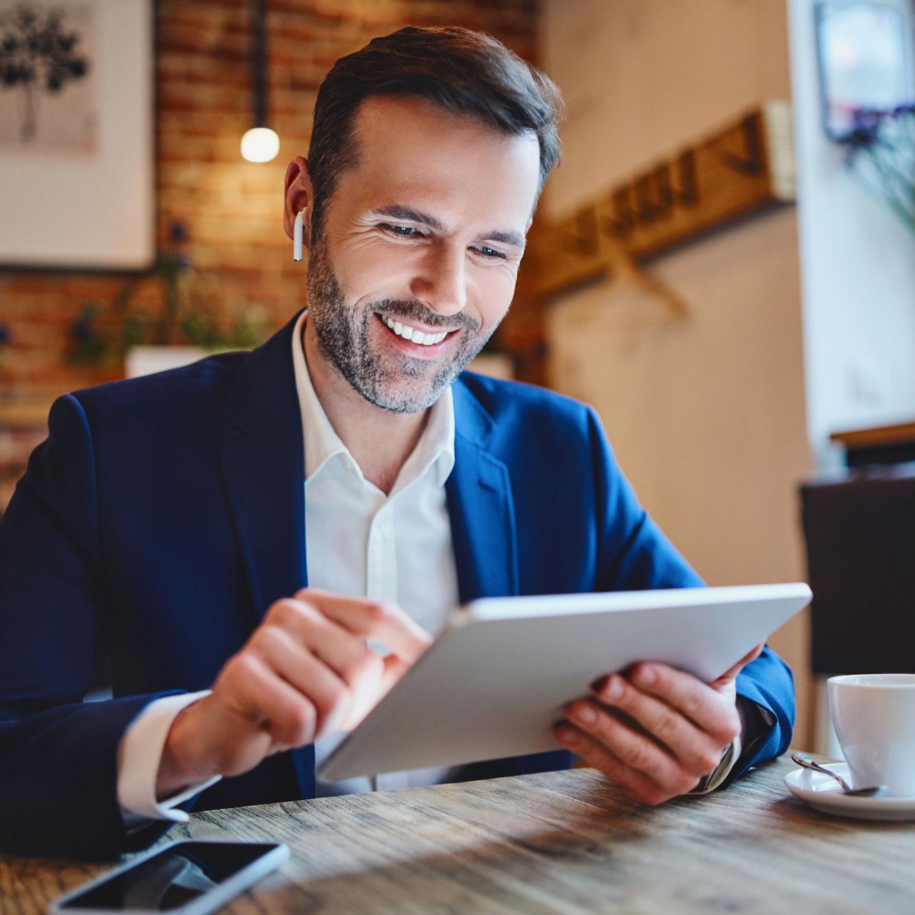 Freundlicher Restaurantinhaber mit Tablet an Tisch sitzend | Delicious Data