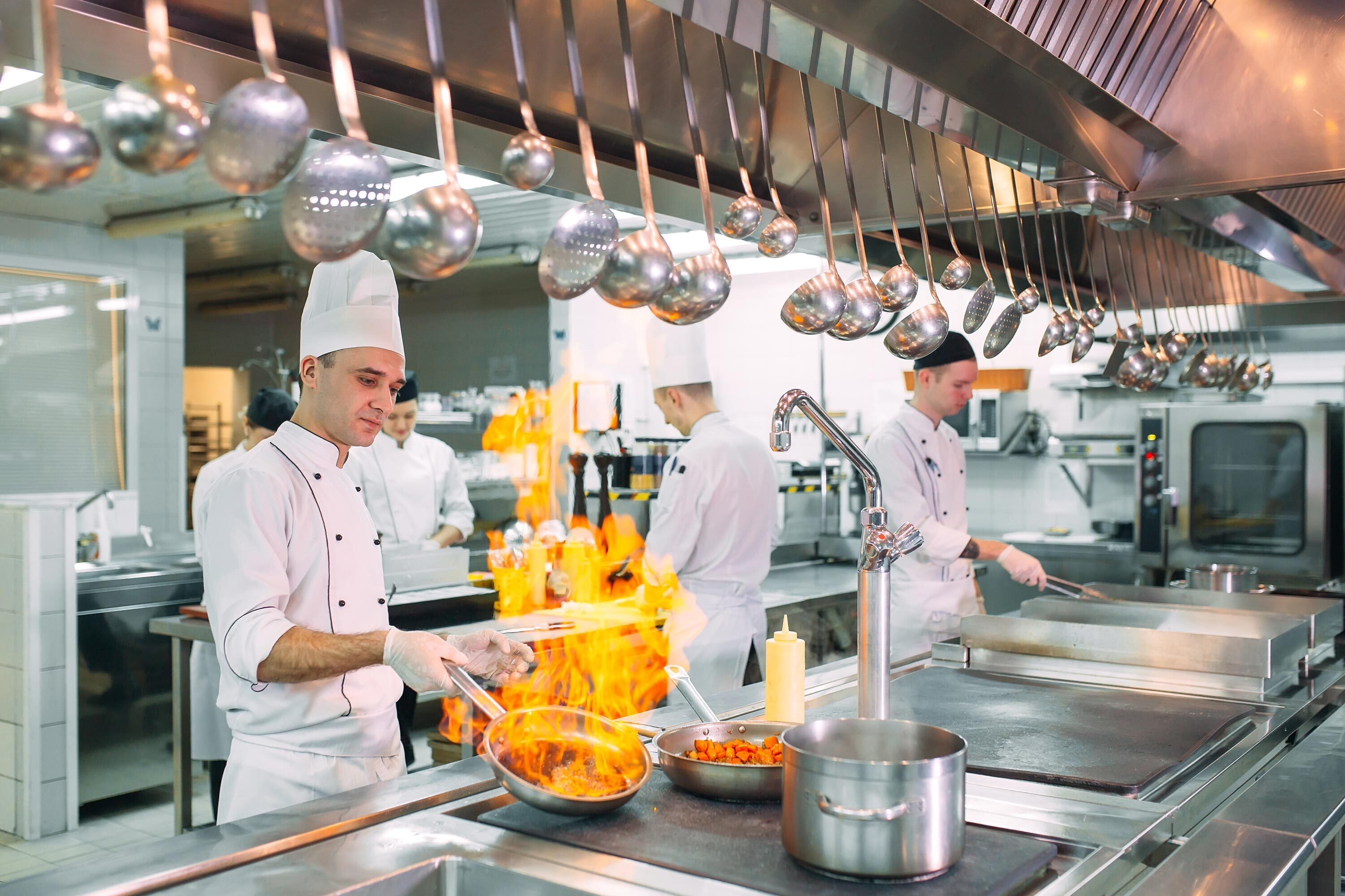 Cook brandishes frying pan with blazing flames in commercial kitchen| Delicious Data