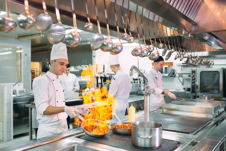 Koch schwenkt Bratpfanne mit lodernder Flammen in Großküche| Delicious Data