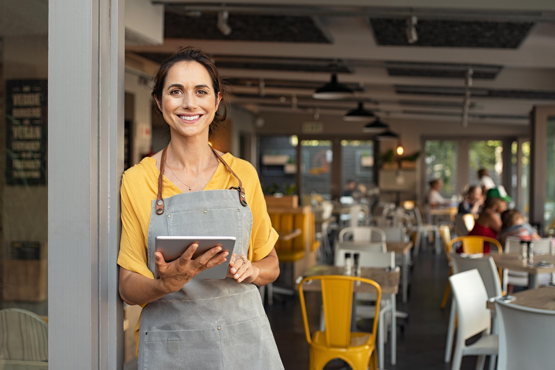 Servicemitarbeiterin empfängt Gäste am Restauranteingang  | Delicious Data