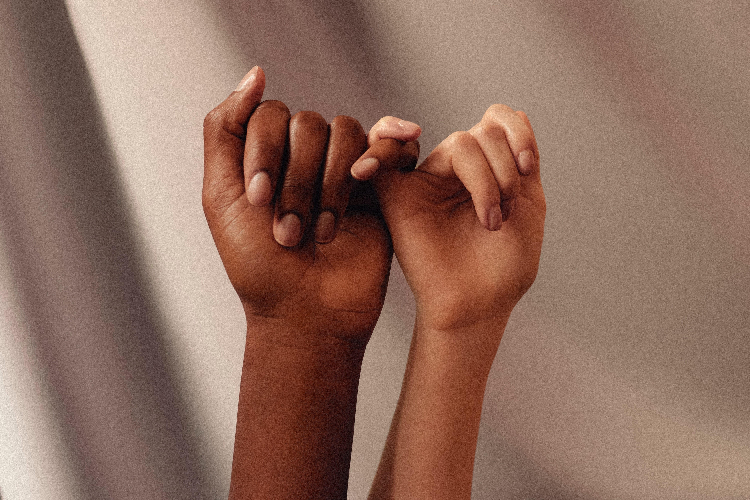 BIPOC women's hands with linked fingers
