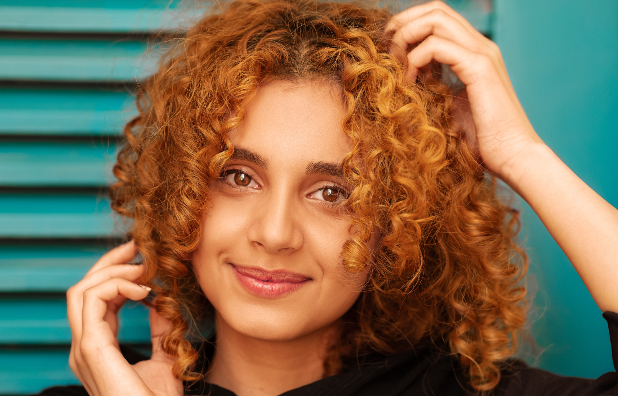 BIPOC middle eastern woman with red curly hair