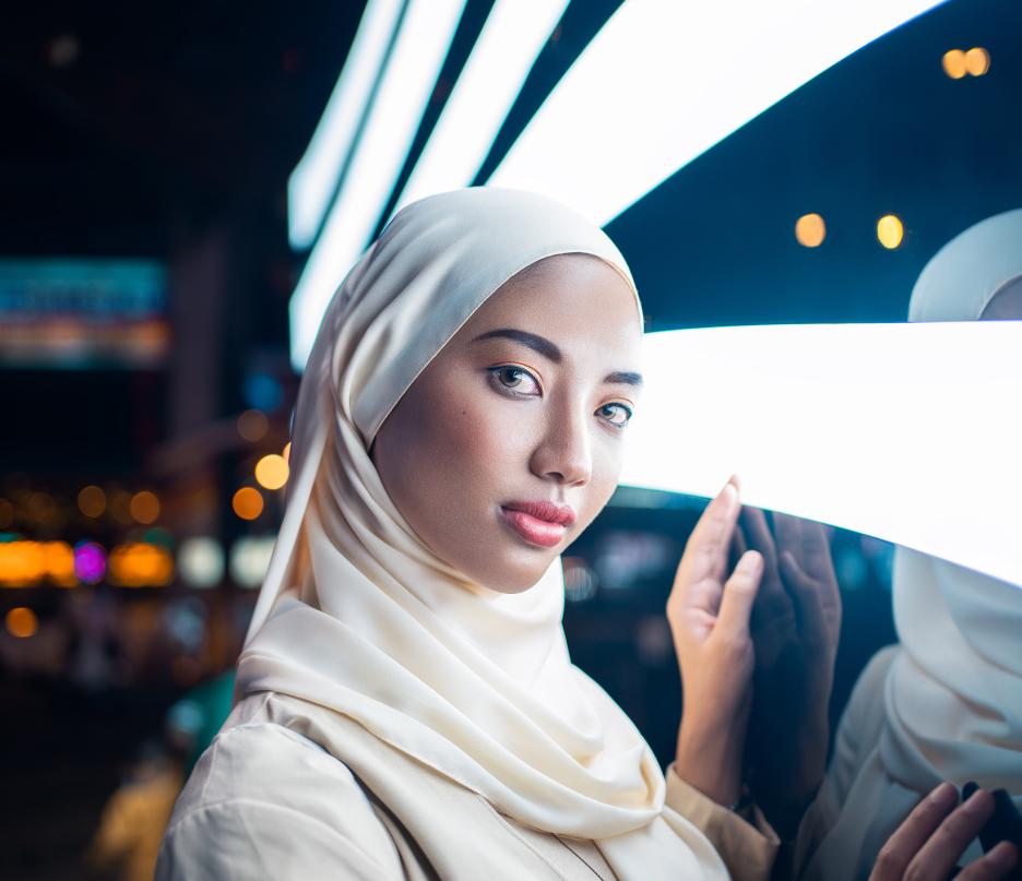 BIPOC woman - asian muslim wearing hijab next to neon lights