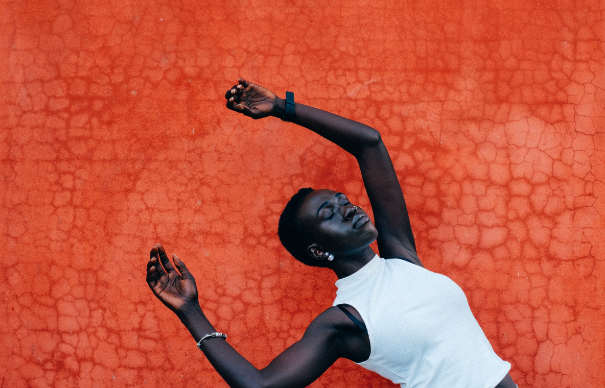 Strong Black Woman with white tank top against textured orange wall