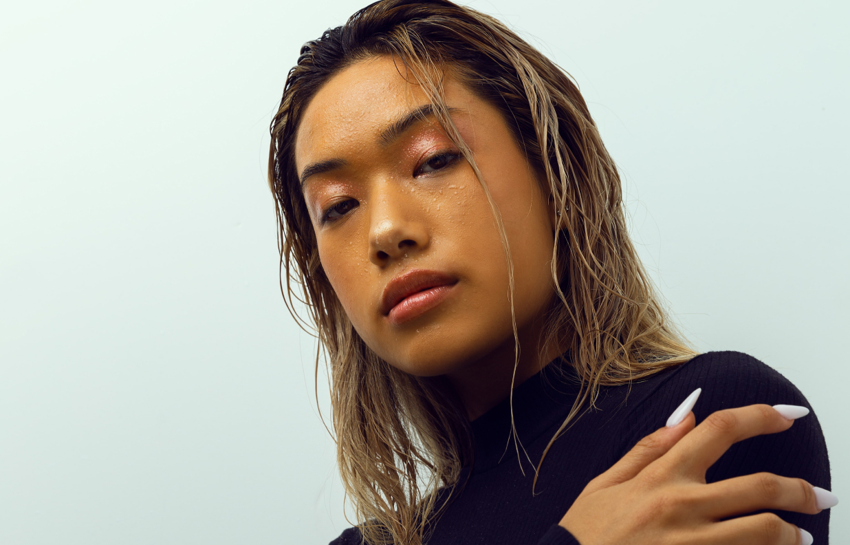 Close up of tough asian woman with wet blonde hair and long fingernails