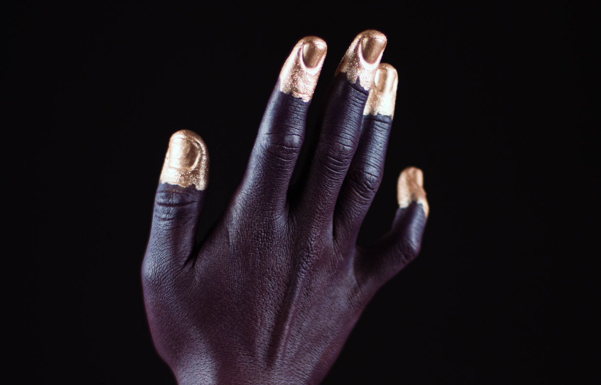 close up of black woman's hand with gold fingertips