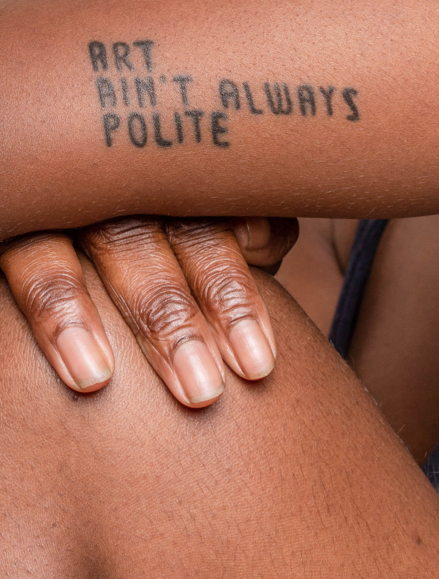 Black woman with tattoo that says art ain't always polite