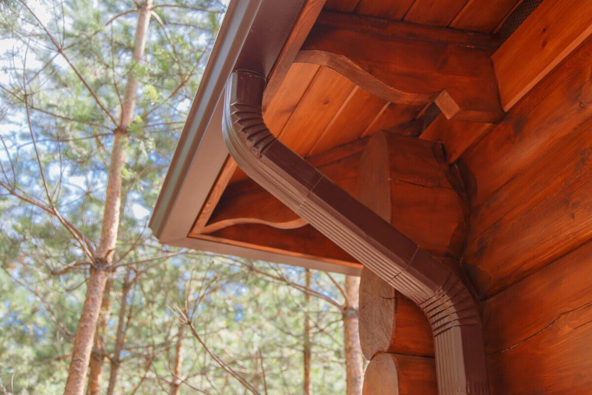 Angle extérieur d'une gouttière neuve installée sur une charpente en bois massif.