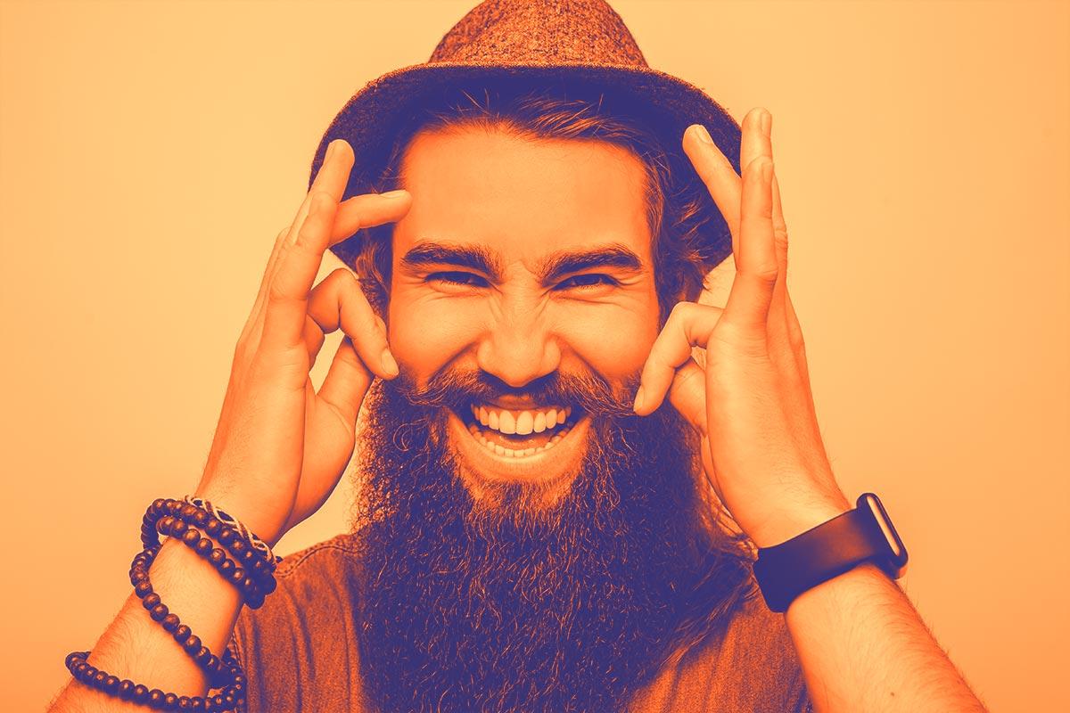 Un monsieur à la barbe bien fournie souriant tenant ses moustaches du bout des doigts