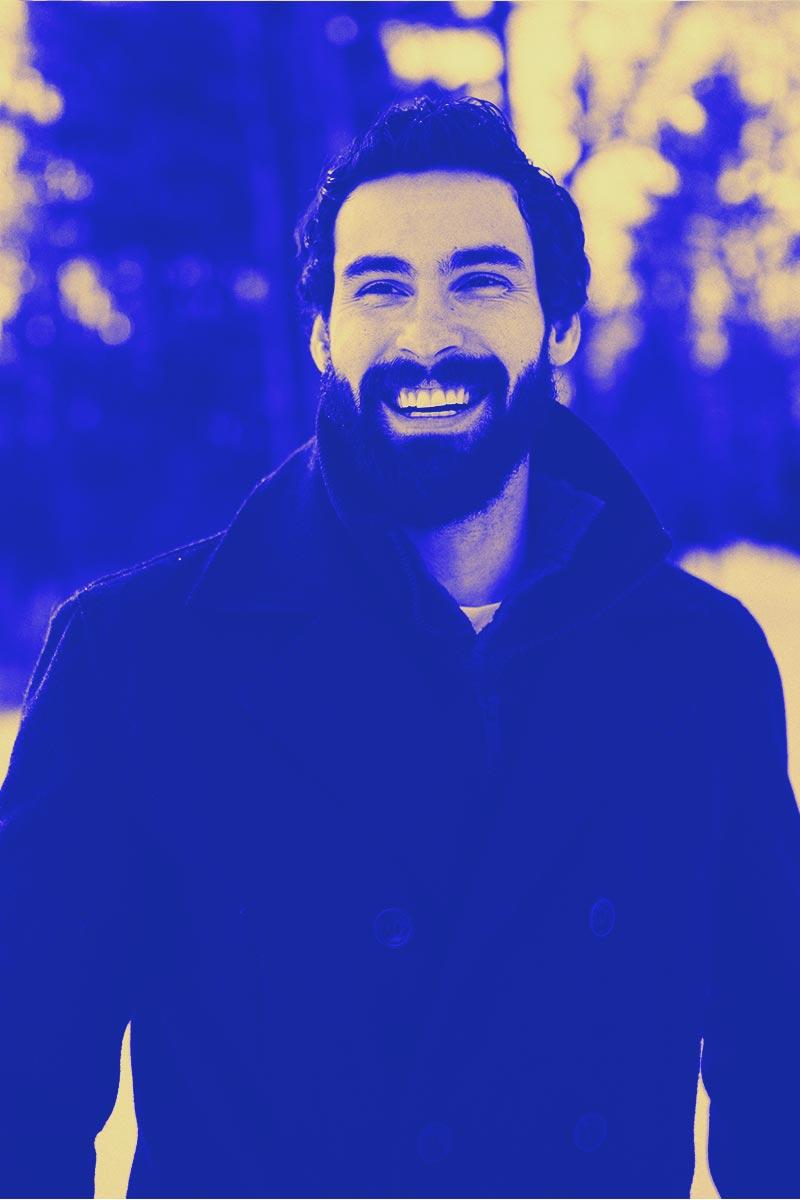 Un homme blanc barbu avec une barbe fournie et une dentition parfaite