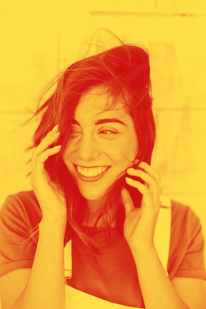 Image d'une femme les cheveux dans le vent arborant un immense sourire