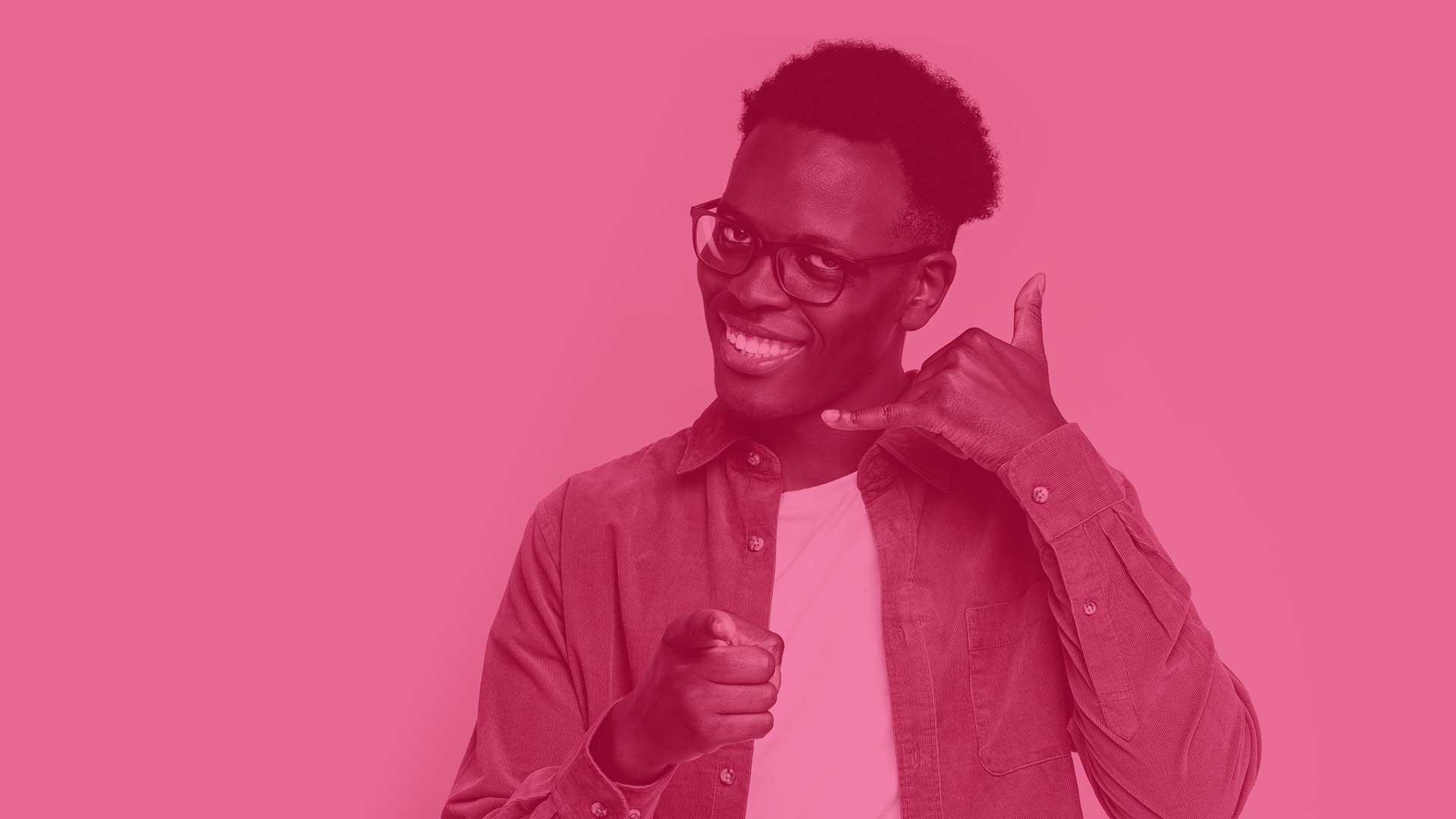 Image d'un homme noir avec des lunettes, souriant et utilisant sa main comme téléphone