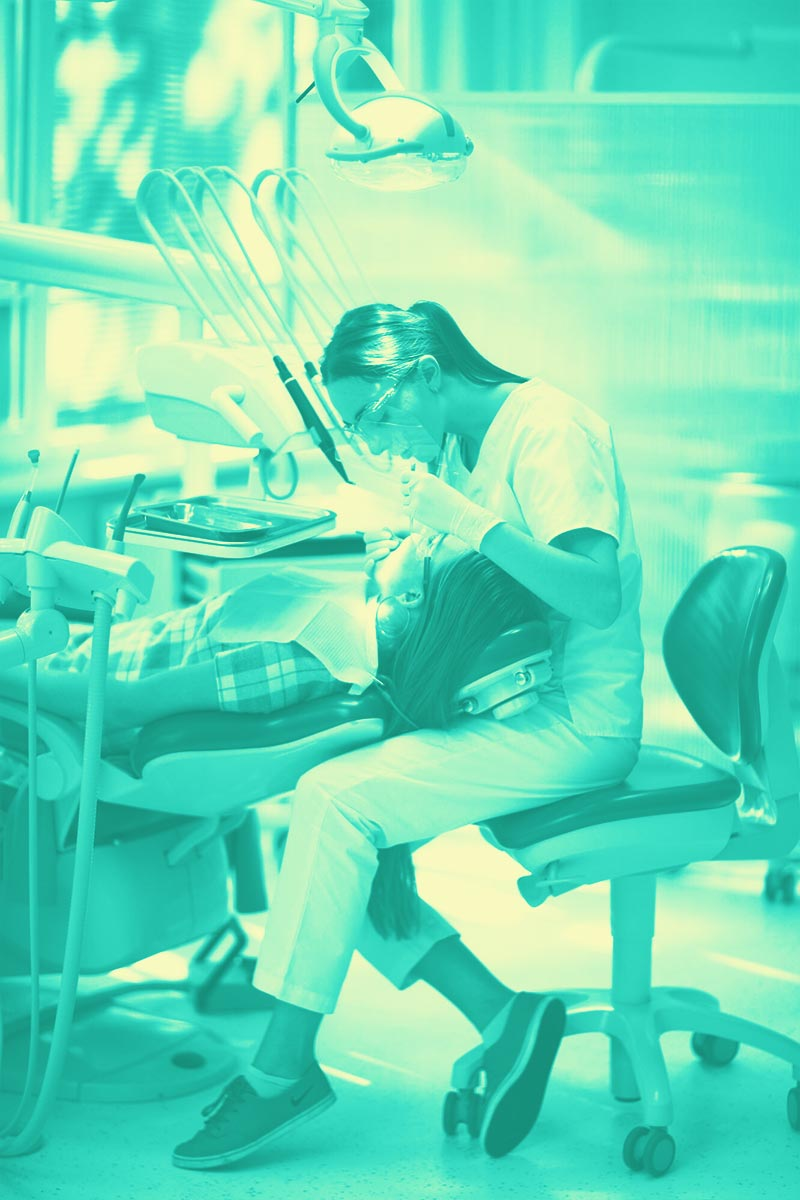 Image d'une dentiste en plein travail avec un patient à la Dental Family