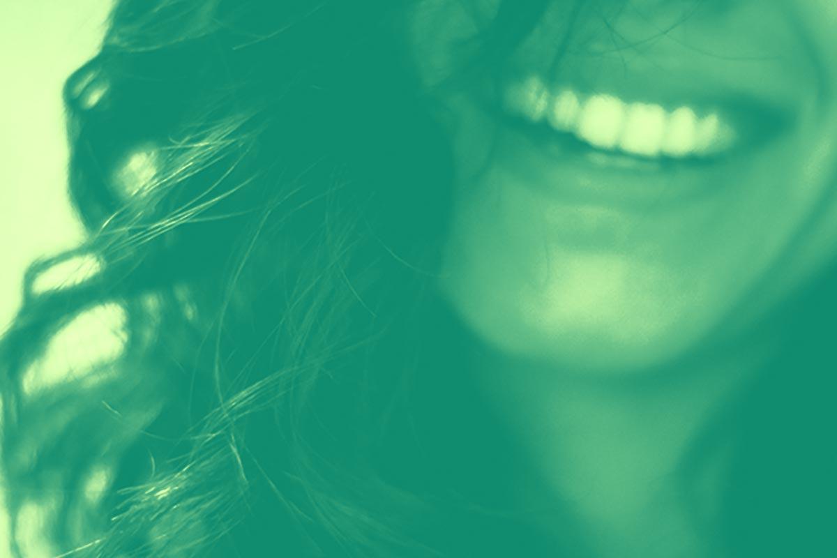 Image d'une femme dont on ne voit que la moitié du visage ayant un large sourire