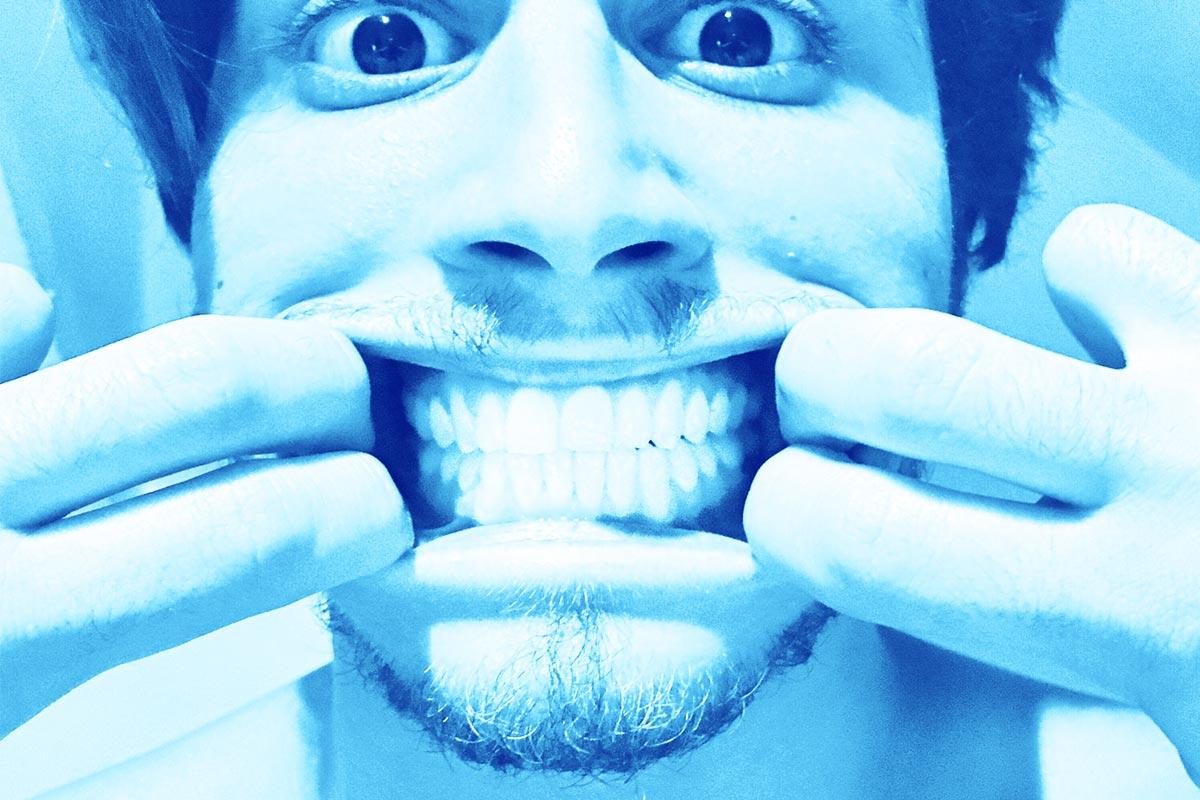Image d'un homme ouvrant bien grand la bouche à l'aide de ses doigts