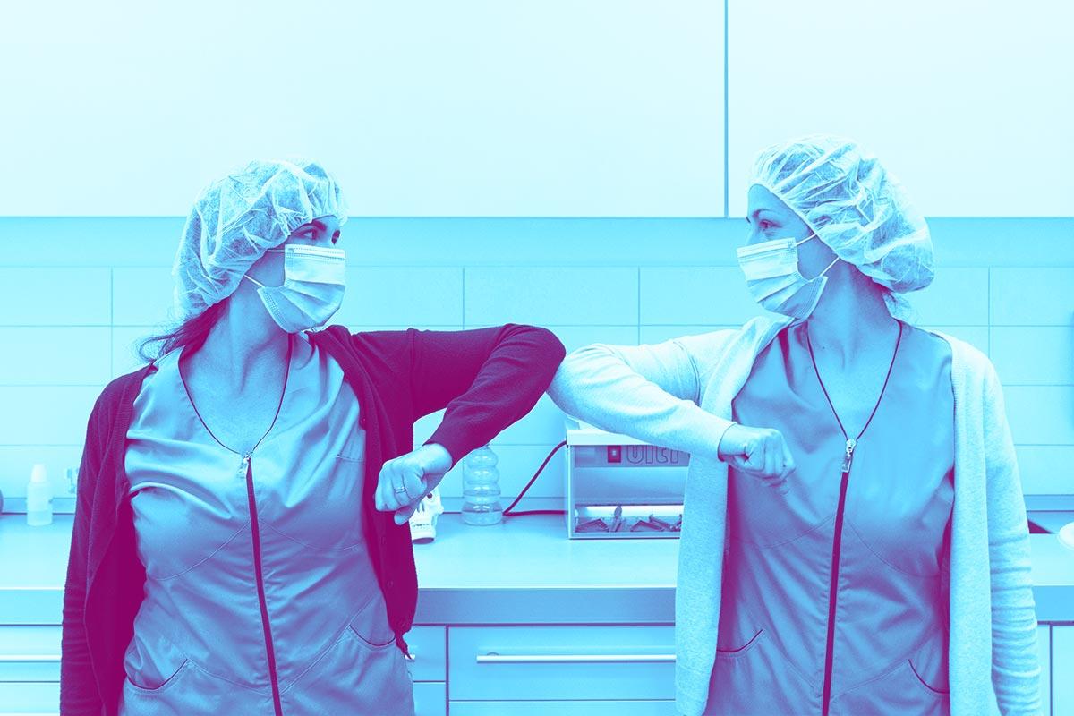 Deux dentistes se saluant avec les coudes pour respecter les gestes barrières