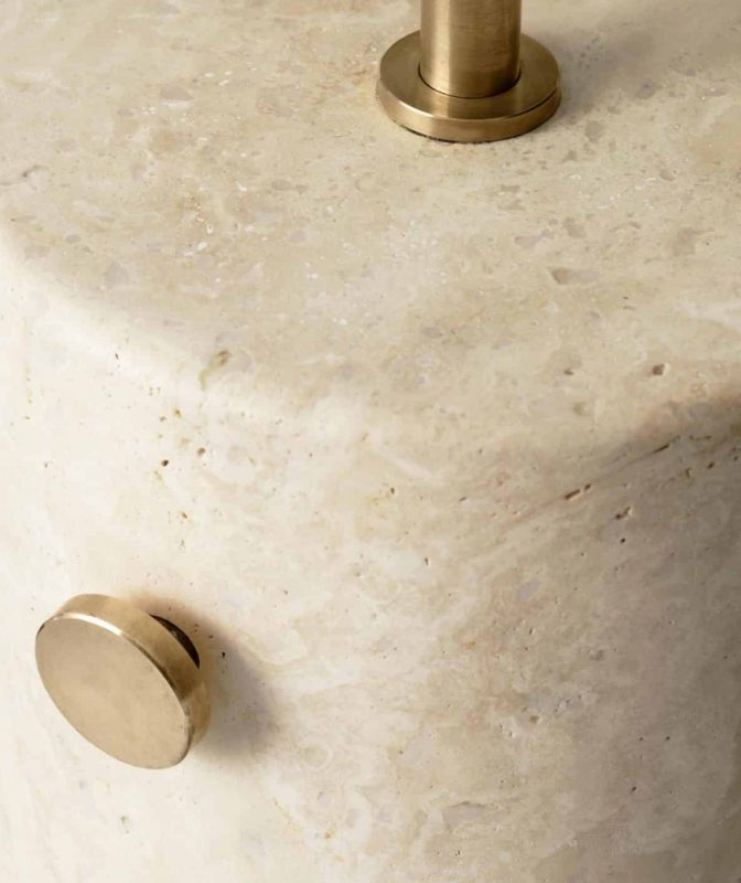 Close-up of the travertine base with brushed brass details of the JWDA floor lamp by Menu