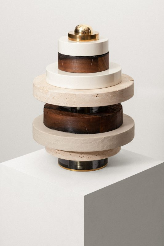 An abstract object of stacked oak, travertine and MDF rings on a brass rod by Vaust Studio