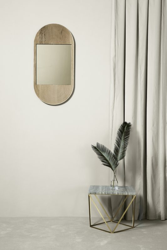 Wooden, oval-shaped June mirror by Coil + Drift in a room setting with glass side table and light grey curtians