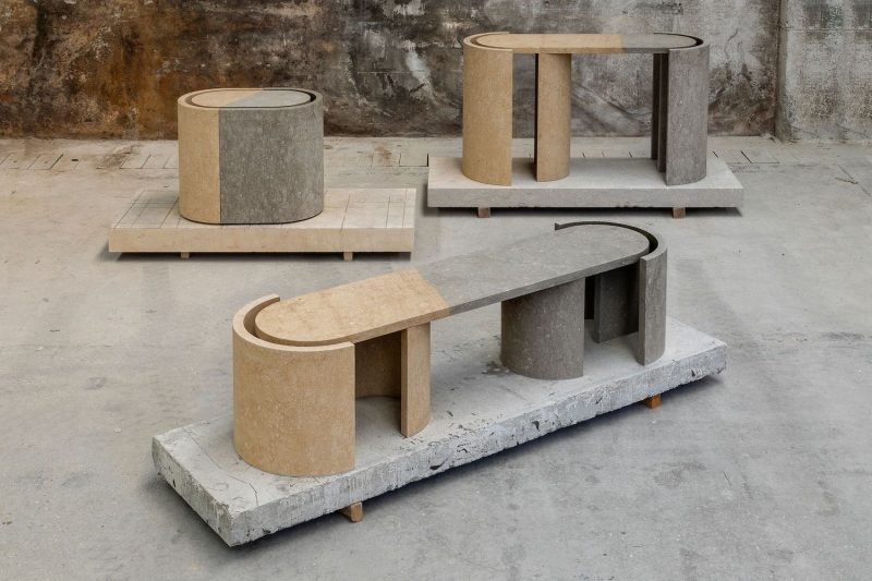 Three oblong-shaped side tables by BVXSY made from a beige and a grey stone in a warehouse setting