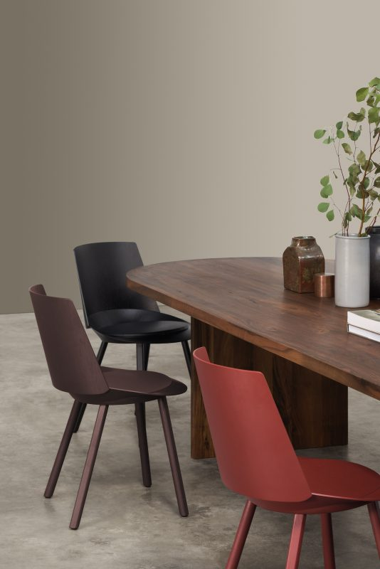 Detail of the oblong shaped Ashida table made from walnut and dining chairs in red, brown and black
