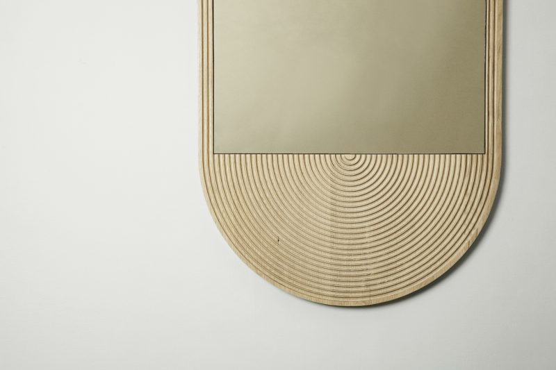 Detail of June mirror by Coil + Drift featuring concentric engravings in the bright wood