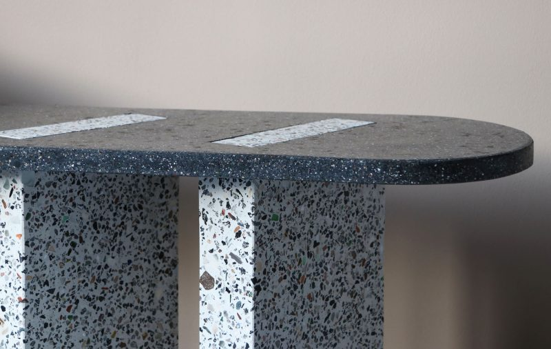 Detail of the grey-black, oblong-shaped Bottom Ash table featuring two types of terrazzo-style material made from bottom ash.