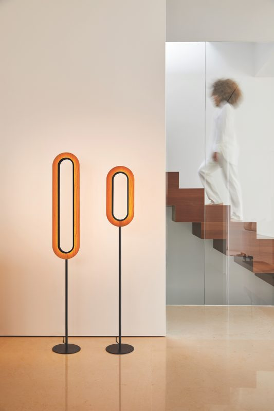 Two oblong shaped Lens floor lights in a room setting with a staircase in the background