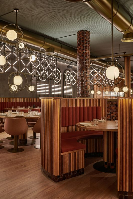 Seating booths and dining area in the Piur pizza restaurant with wooden wall panelling, brown mosaic tiles and industrial-style lighting
