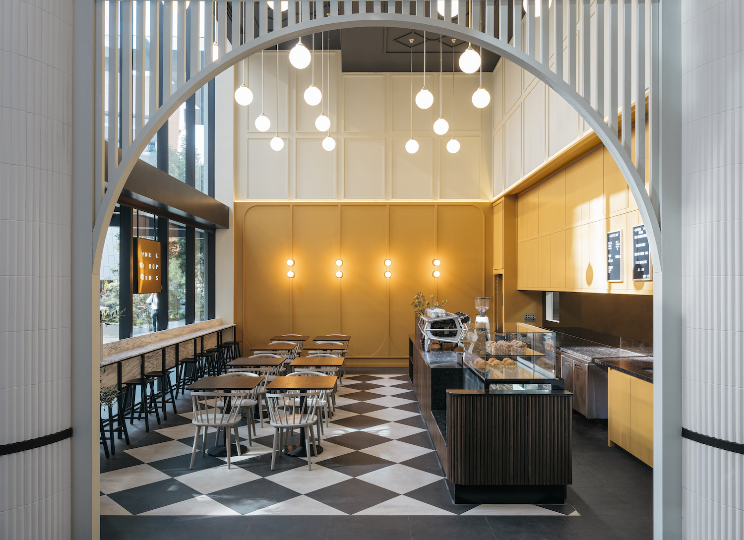 A cafe space with high ceilings and yellow wood panelling