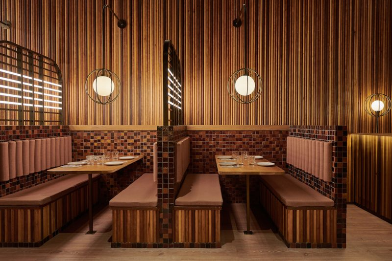 Seating booths in the Piur pizza restaurant with wooden wall panelling, brown mosaic tiles and industrial-style lighting