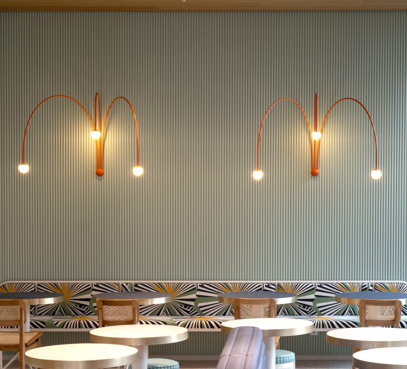 Seating area in the Lilli P. restaurant in Munich with Gubi chairs, round dining tables and a seating bench featuring a fabric by Derkek Castiglioni with a green wood panelled wall featuring lights by Michael Anastassiades