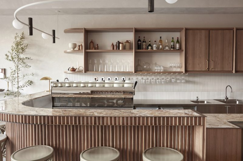 Bar area in the Via Porta cafe featuring a counter with wooden wall panelling, spotlight on a curved railing and mud green wooden bar stools