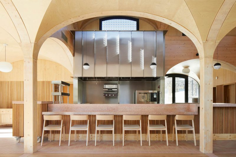Seating area along a bar counter in the Wildernesse restaurant with an arched ceiling and pillars cladded with wood