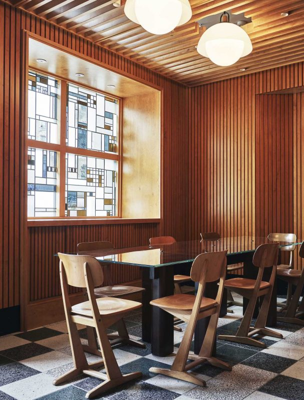 Meeting room in the Sister Hotel NYC with old school chairs, wooden wall panelling and a stained glass window