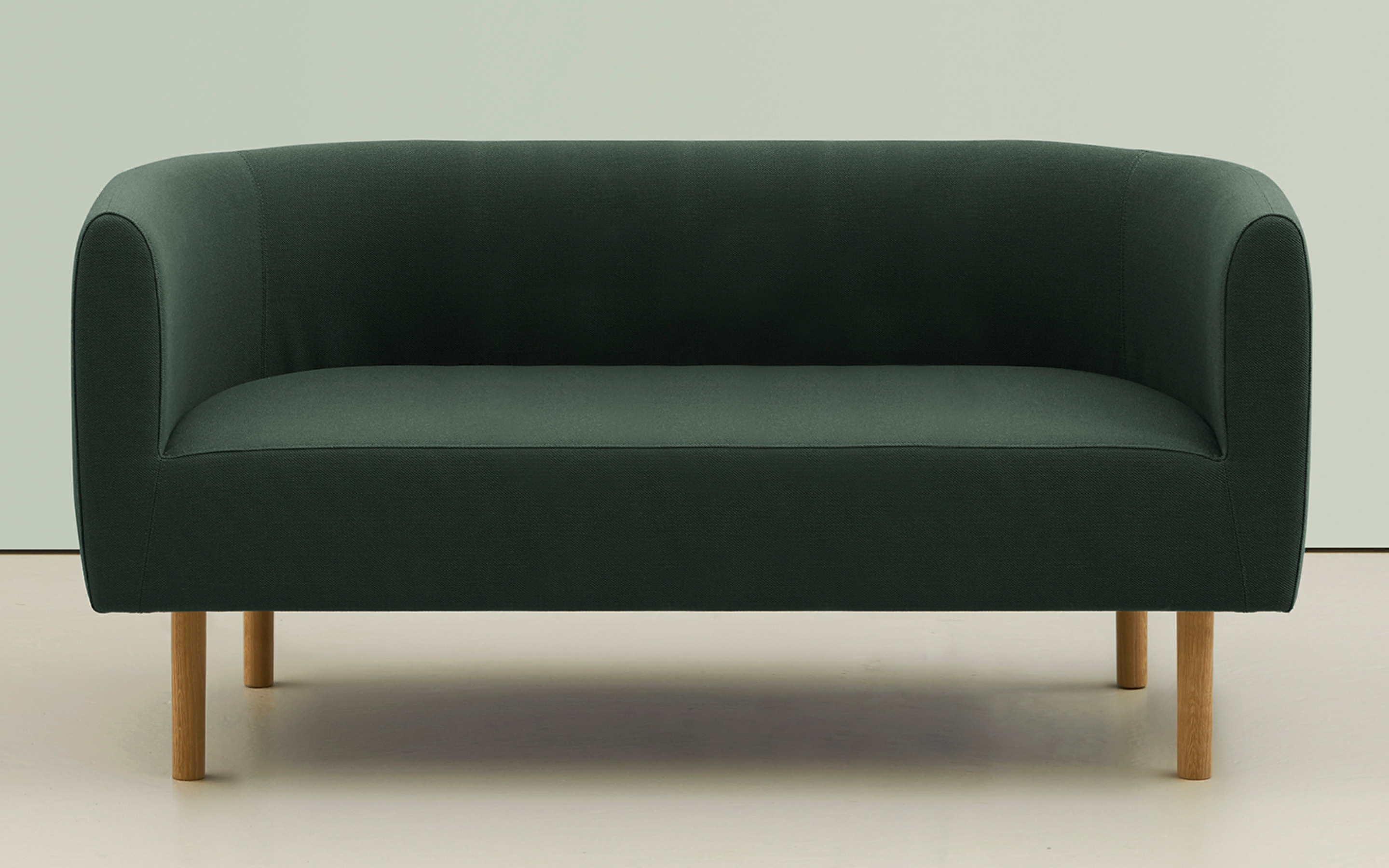 Green hm45b Juno sofa with curved backrest and solid wood feet