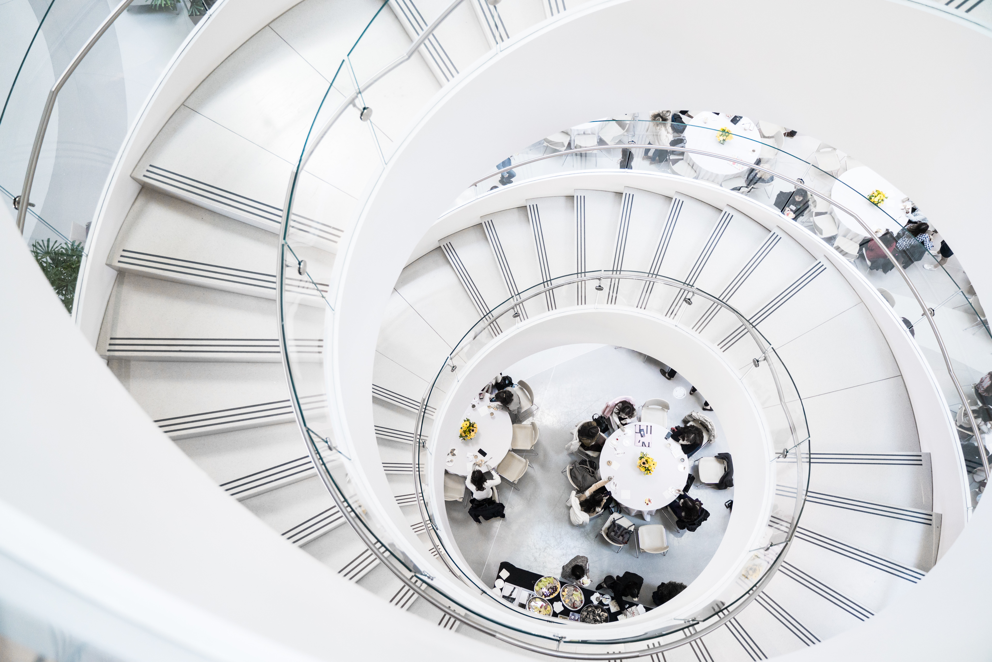 Spiral staircase looking down onto people around tables.