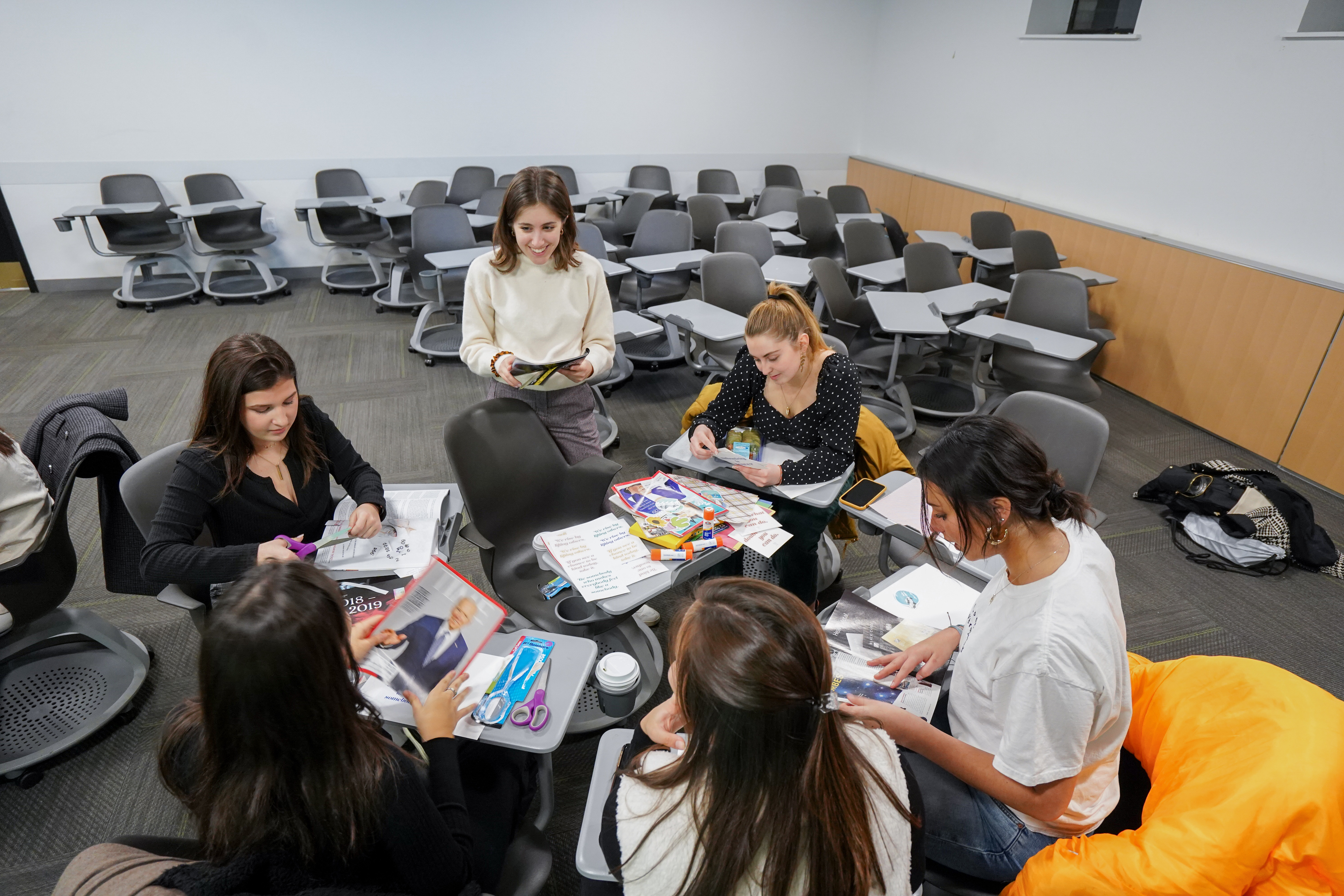 Six women sitting together in a circle and making vision boards.