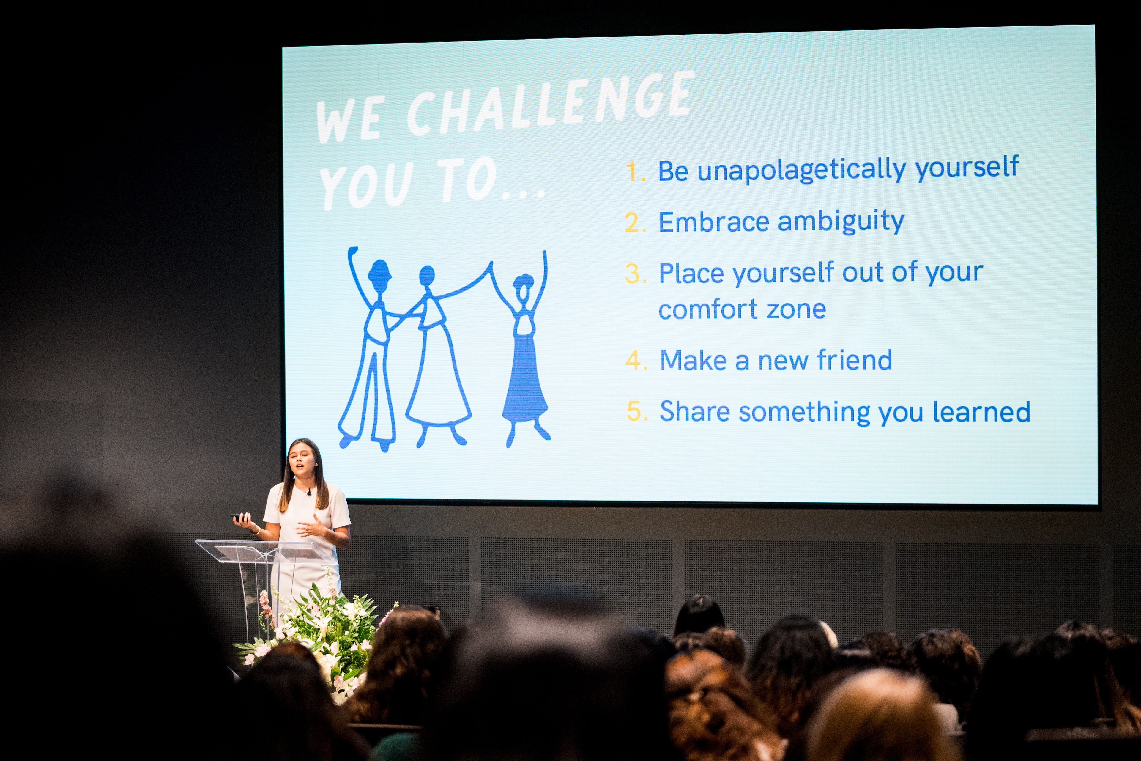 Woman giving a presentation to a crowd in a large auditorium.