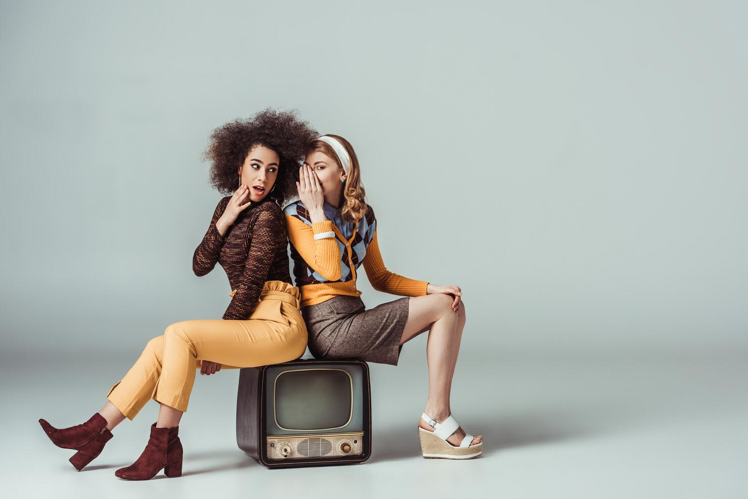 image of two girls sitting on an old tv gossiping