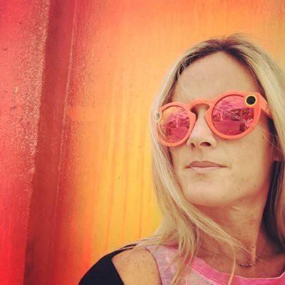 Navah Berg wearing sunglasses with orange background
