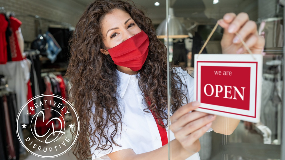 Creatively Disruptive - girl pulling open sign on door wearing a mask