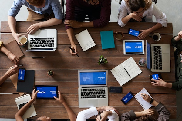 SEO Agency team sits in a meeting and collaborates over their laptops