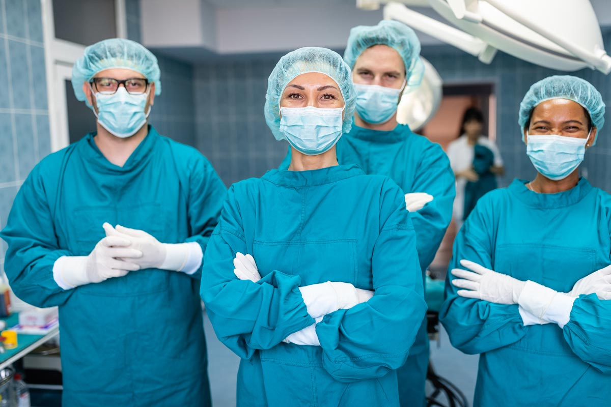 A group of surgeons in a hospital operating theatre.
