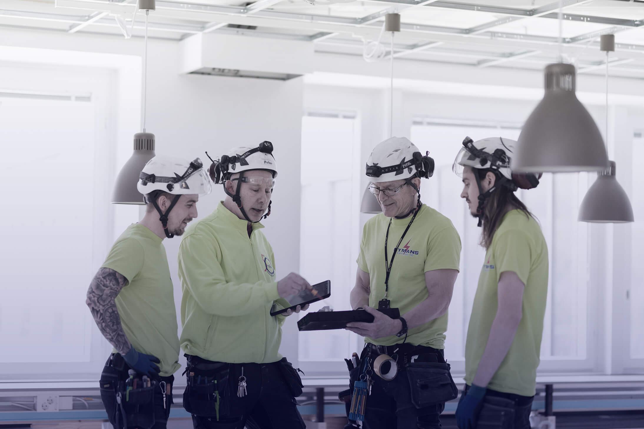 Fyra män i ett arbetslag har arbetsplatsmöte.