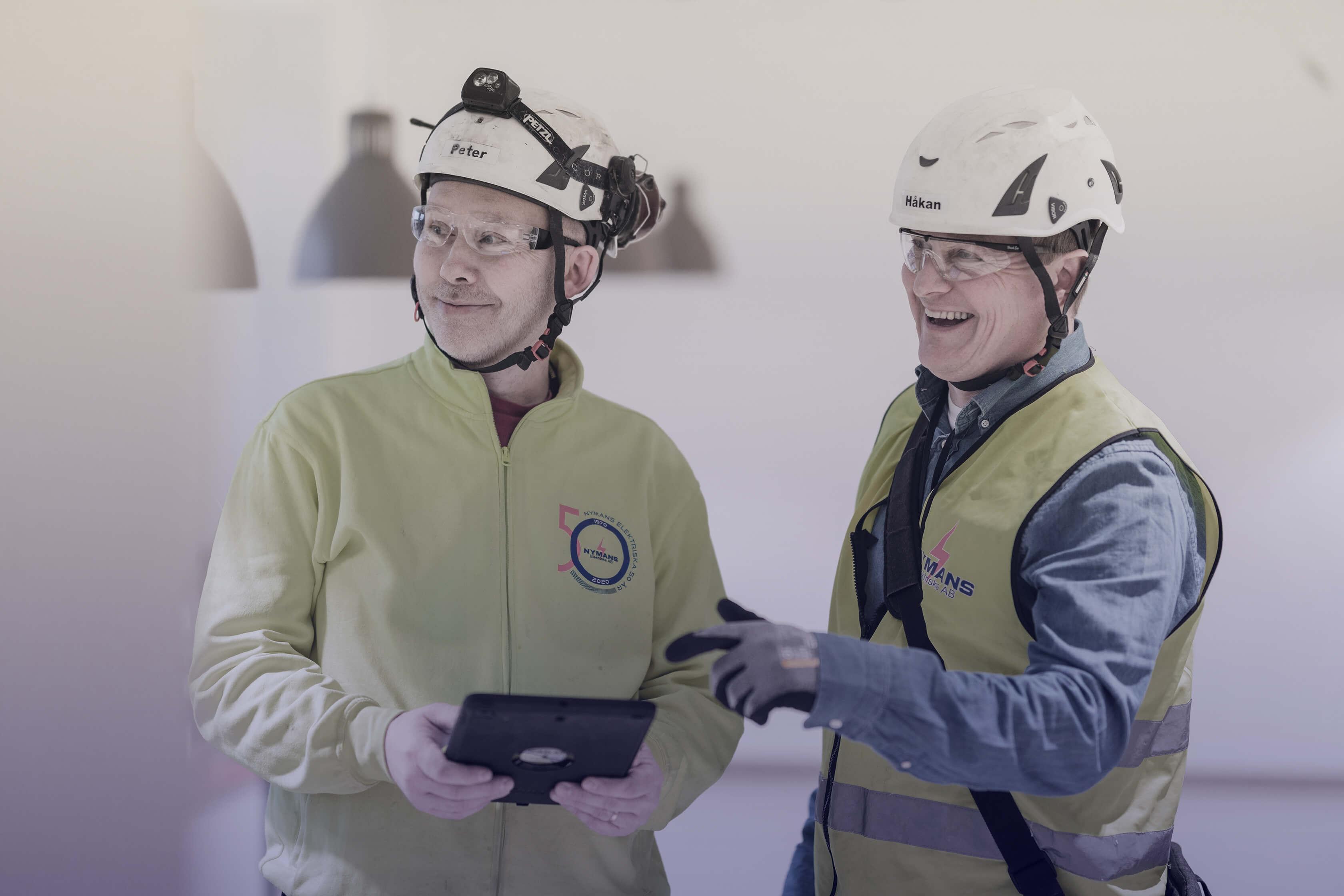 Två glada män med arbetskläder och skyddshjälmar.