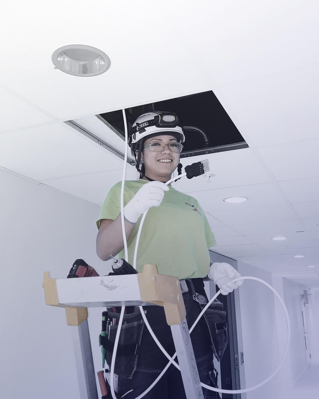 Ung kvinna står på stege och håller i el-kabel