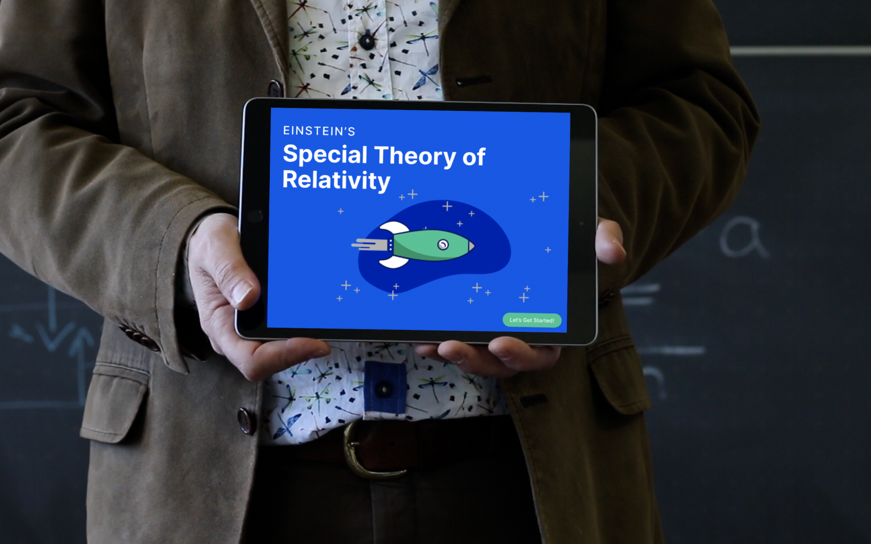 """A teacher in front of a blackboard holds a tablet in his hand displaying an app entitled """"Einstein's Special Theory of Relativity"""""""