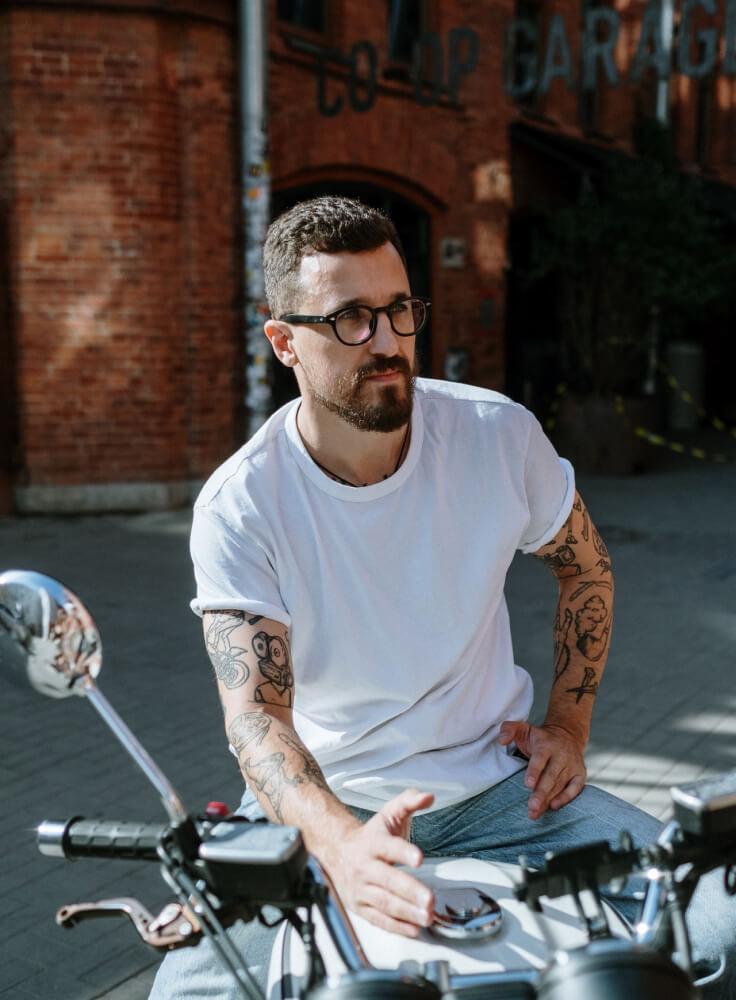 Junger Mann sitzt auf seinem Motorrad und vermittelt ein Freiheitsgefühl